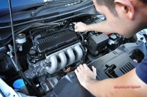 mechanic inspects and repairs car engine