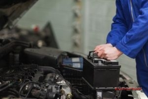 mechanic holds car battery
