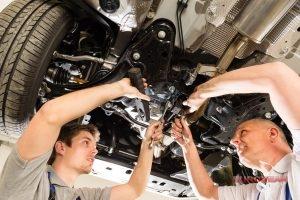 two mechanics work underneath a car