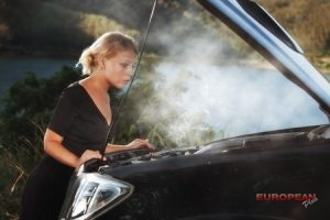 woman looks at her engine overheating in her car