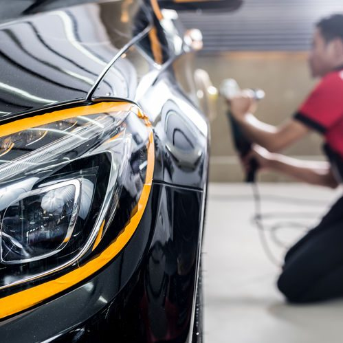 Close up of the headlight of a black vehicle with a blurred mechanic that's polishing the rear siding of the car in the back.