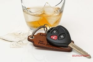a photo of car keys next to an alcoholic beverage