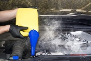 mechanic pours coolant into radiator to cool down overheating engine